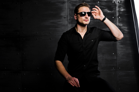 Studio portrait of stylish man wear on black shirt and glasses against steel wall.