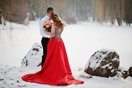 Amazing couple in winter fairytale forest in love. Girl in red beautiful dress. Valentines Day theme.