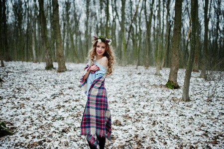 Curly cute blonde girl with wreath in checkered plaid at snowy forest in winter day.