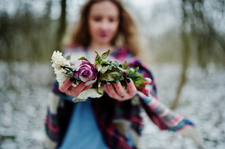 Ggirl holding wreath on hands at snowy forest in winter day. Stock Photo