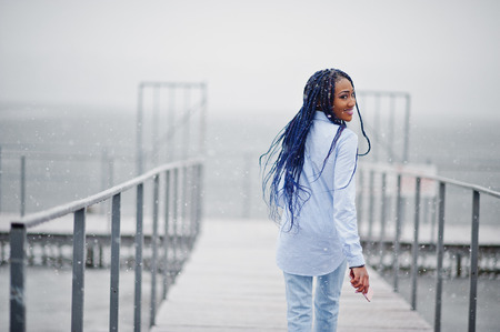 Stylish african american girl with dreads holding mobile phone at hand, outdoor on pier against frozen lake at snowy weather.