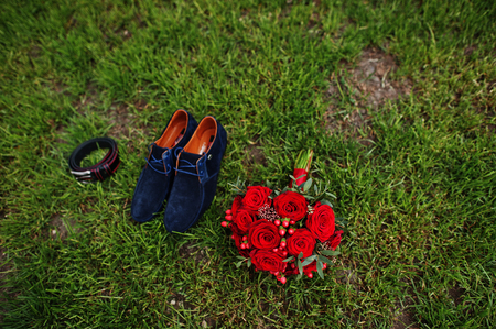 Wedding red bouquet laying on the grass along with groom shoes and a belt.