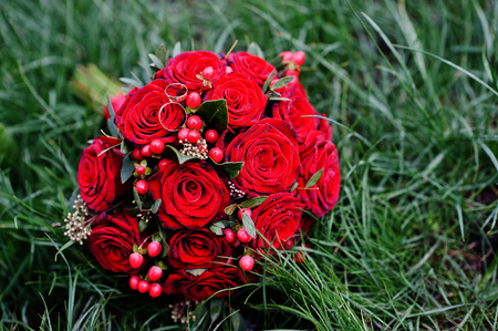 Close-up photo of a wedding bouquet made of red roses and berries.