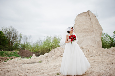 Portrait of a bride holding a wedding bouquet of red flowers and posing alone in sand quarry.