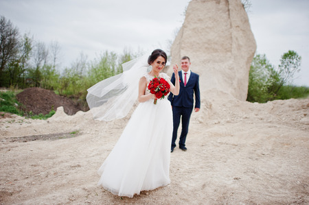 Young wedding couple posing in sand quarry on their wedding day. Stock Photo