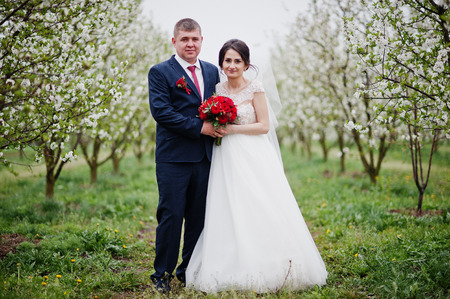 Gorgeous newly married couple posing in the blossoming garden on their weedding day.
