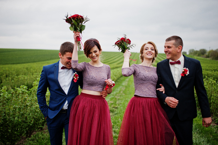 Groomsmen and bridesmaids having fun and posing in blacckcurrant field.