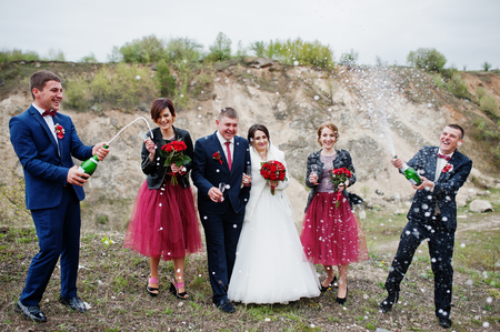 Wedding couple, groomsman and bridesmaids looking at best man opening the champagne bottle in sand quarry.