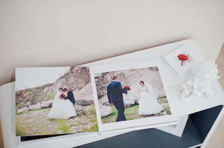 Pages of elegant photobook or wedding album on a small table.