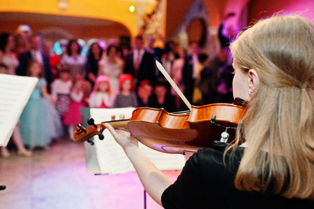 Close-up portrait of a beautiful young female violinist playing violin on the wedding in restaurant. Banco de Imagens