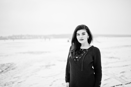 Brunette plus size model at red against frozen lake on winter day.