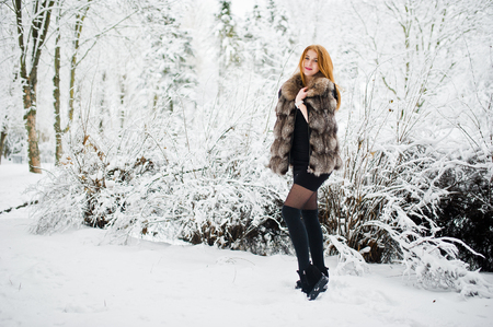 Red haired girl in fur coat walking at winter snowy park.