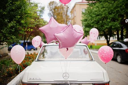 Hai, Ukraine - 07 November,2017: white retro Mercedes-Benz W114 with pink balloons riding on th streets of the town. Editorial