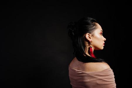 Studio portrait of back hairdress brunette girl on black background.