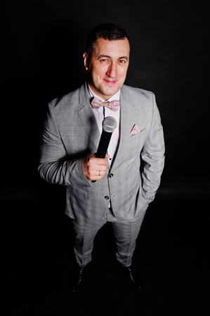 Handsome man in gray suit with microphone against black background on studio. Toastmaster and showman.