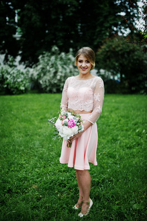 Perfect girl in pink dress with bouquet at hands.