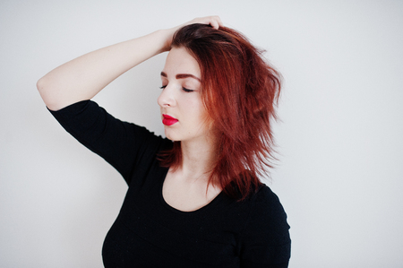 Red haired girl on black dress tunic against white wall at empty room.