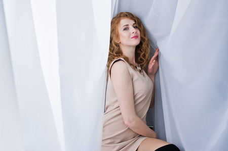 Curly hair girl on beige dress posed at white curtains. Stock Photo