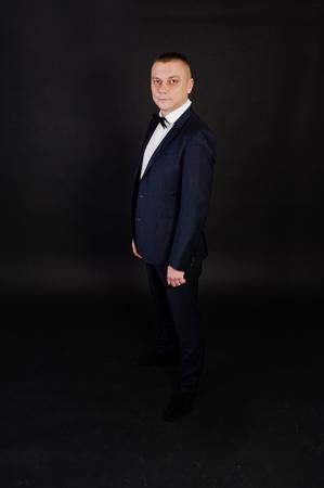 Stylish man in suit posed on studio isolated on black. Stock Photo