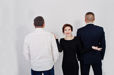 Elegance woman in black evening dress with two man in suit posed on studio isolated on white. Trio band. Stockfoto