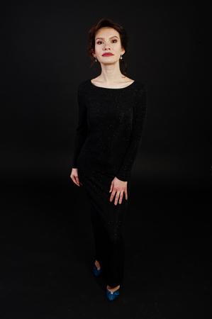 Elegance woman in black evening dress posed on studio isolated on black.