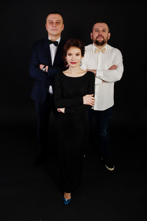 Elegance woman in black evening dress with two man in suit posed on studio isolated on black. Trio band.