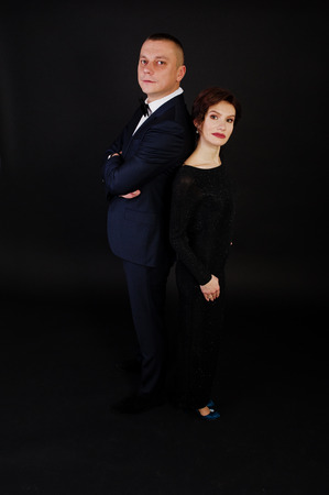 Elegance woman in black evening dress with man in suit posed on studio isolated on black. Duet couple of two. Stock Photo