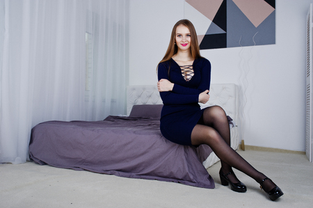 Studio shot of brunette girl in tunic at bed.