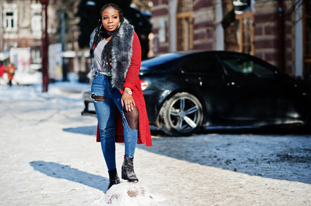Rich african american girl in red coat and fur on winter street at sunny weather against black business car. Black stylish woman.