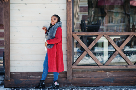 Rich african american girl in red coat and fur against wooden cafe outdoor. Black stylish woman.