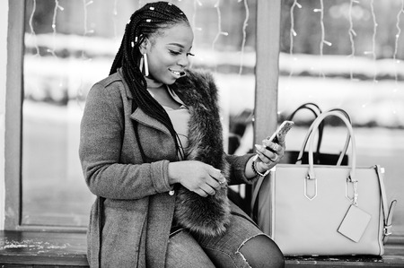 Rich african american girl in red coat and fur sitting at bench with handbag and looking on mobile phone. Black stylish woman with cell gadget.