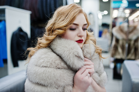 Elegance blonde girl in fur coat at the store of fur coats and leather jackets.   Stock Photo