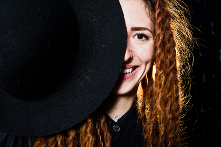 Studio shoot of girl in black with dreads and hat on brick background. Stock Photo