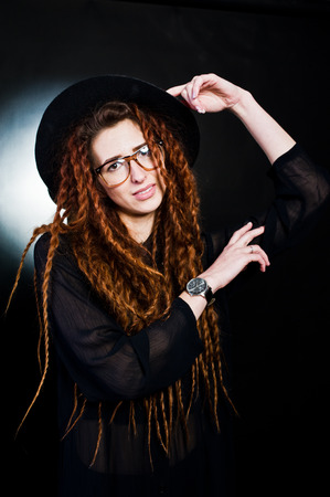 Studio shoot of girl in black with dreads, hat and glasses at black background. Stock Photo