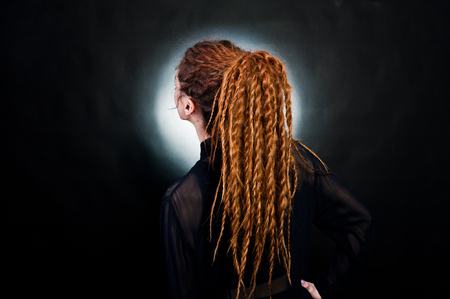 Studio shoot back of girl in black with dreads at black background with nimbus.