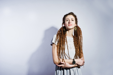 Studio shoot of girl in gray dress with dreads on white background. Stock Photo