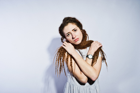 Studio shoot of girl in gray dress with dreads pigtails on white background.