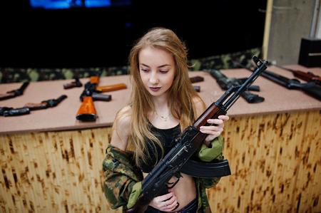 Girl with machine gun at hands on shooting range. Stock Photo