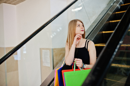 Girl with shopping bags in the mall at the escalator.