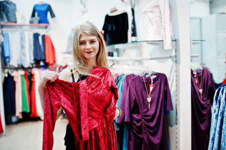 Blonde girl tries a red dress in the boutique.