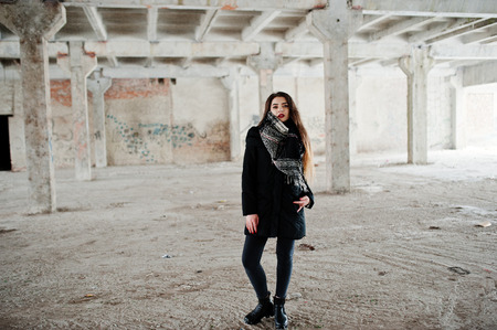 Brunette stylish casual girl in scarf against abandoned factory place.