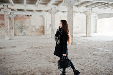 Brunette stylish casual girl in scarf and handbag against abandoned factory place.