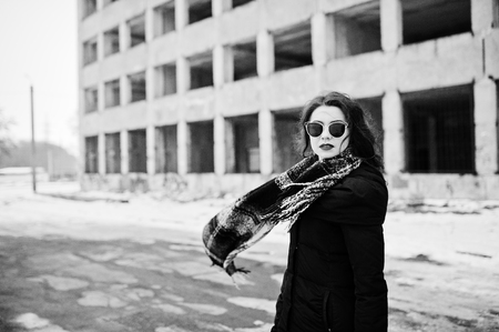 Brunette stylish casual girl in scarf and sunglasses against abandoned factory place. Scarf in air.
