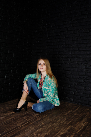 Stylish blonde girl in jacket and jeans against brick black wall at studio. Stock Photo