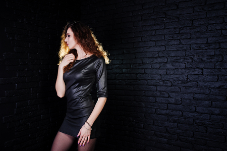 Brunette curly haired long legs girl in black leather dress posed at studio against dark brick wall.