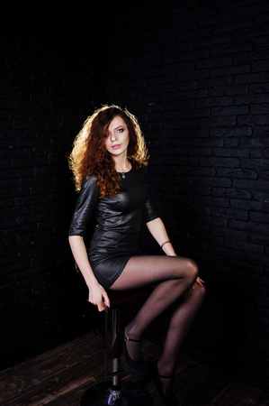 Brunette curly haired long legs girl in black leather dress posed at studio on chair against dark brick wall. Stock Photo