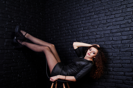 Brunette curly haired long legs girl in black leather dress posed at studio on chair against dark brick wall. Imagens