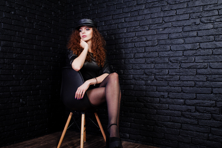Brunette curly haired long legs girl in black leather dress and cap posed at studio on chair against dark brick wall.