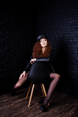 Brunette curly haired long legs girl in black leather jacket with swimmsuit and cap posed at studio on chair against dark brick wall.