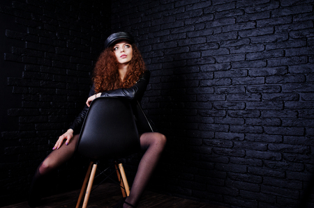 Brunette curly haired long legs girl in black leather jacket with swimmsuit and cap posed at studio on chair against dark brick wall. Imagens - 98098417